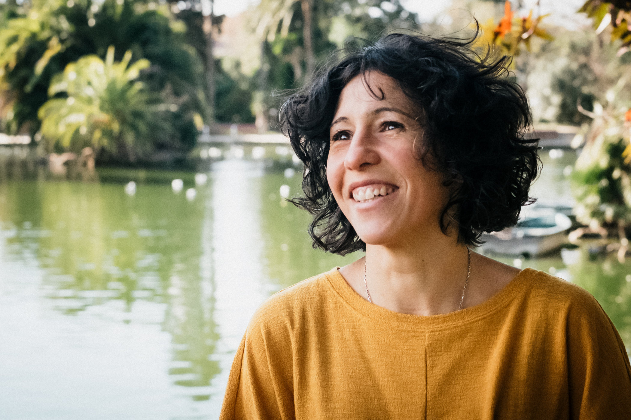 A woman laughing in a park with a lake Ciutadella park at Barcelona, solo portrait picture by Pauline Mattia