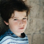 Young boy by a brick wall, picture by Pauline Mattia