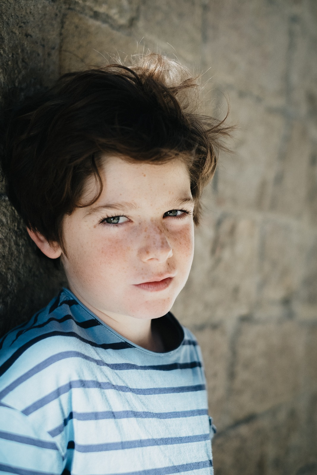 Young boy by a brick wall in Barcelona, solo portrait picture by Pauline Mattia