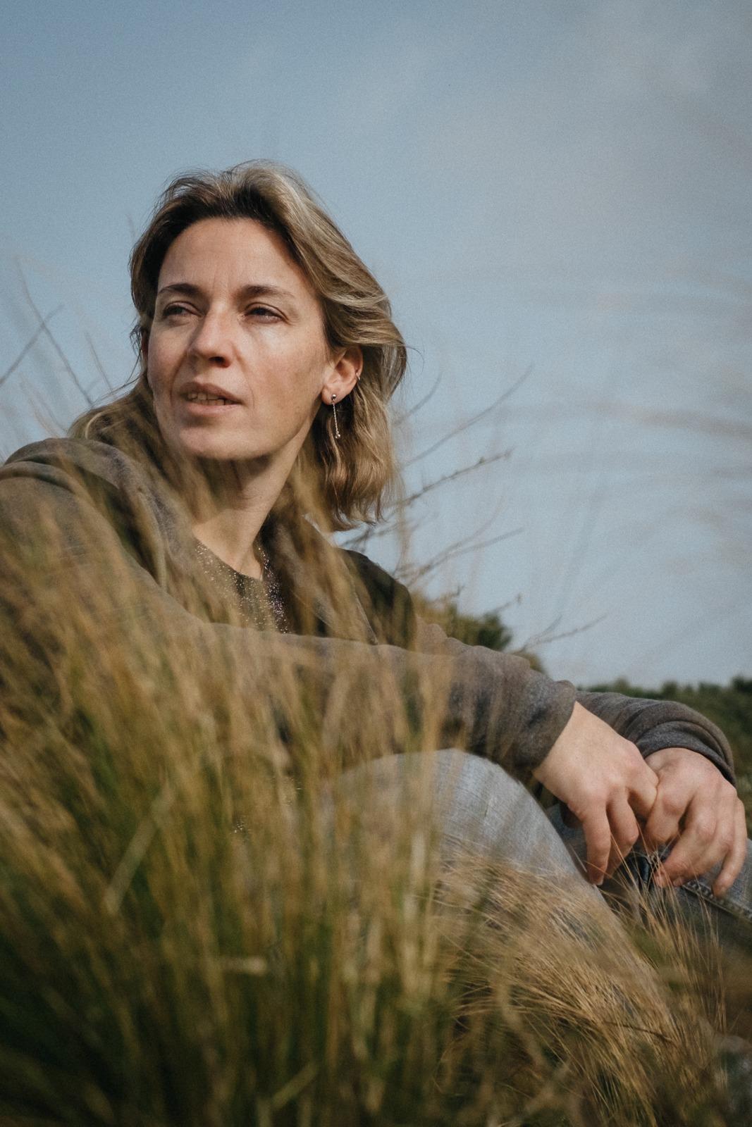 Woman sitting in a dune marbella beach Barcelona solo portrait picture by Pauline Mattia