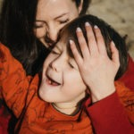 Mother and son laughing together on the beach by Pauline Mattia